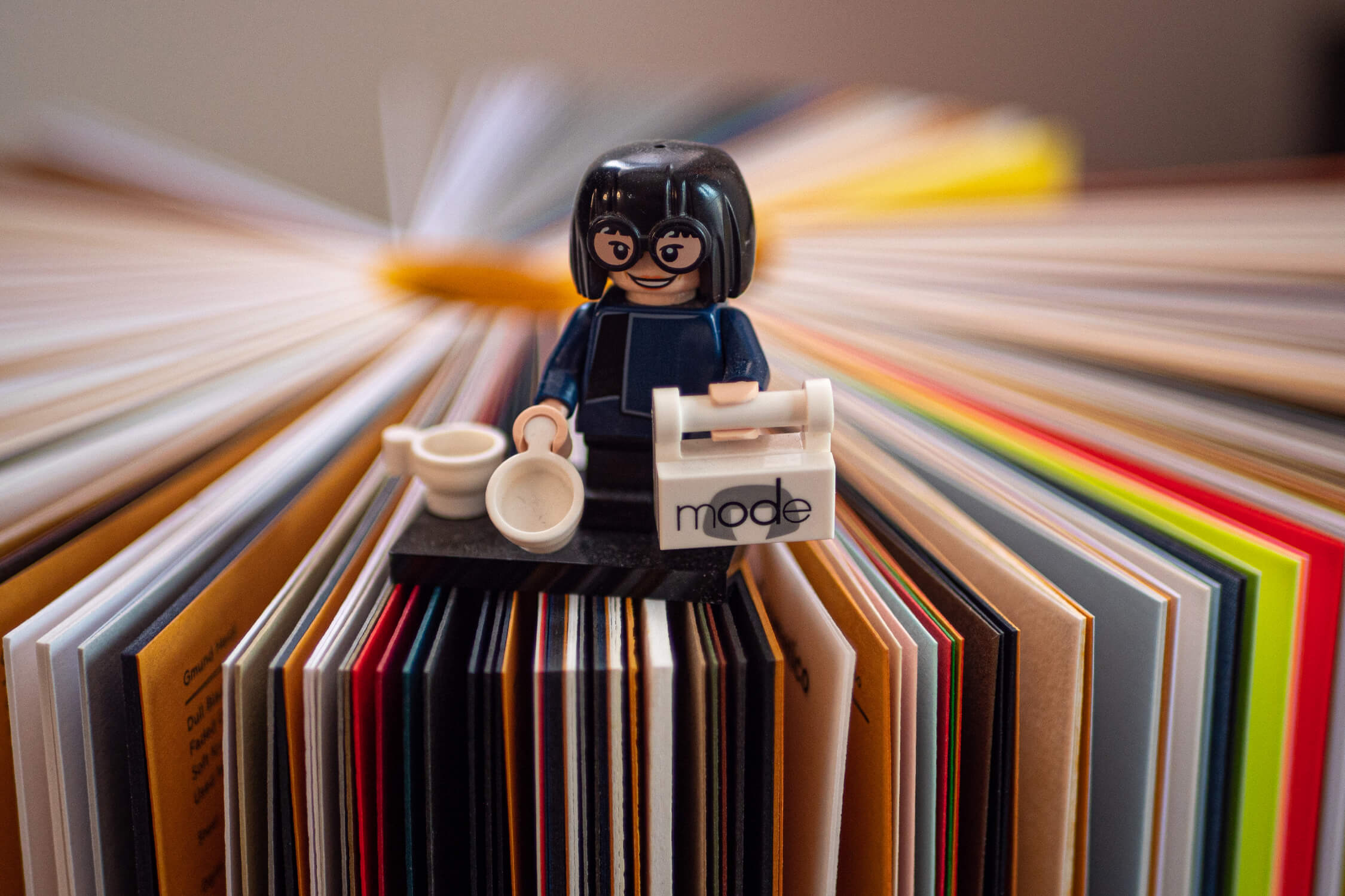 A lego figure standing on a GF Smith paper book